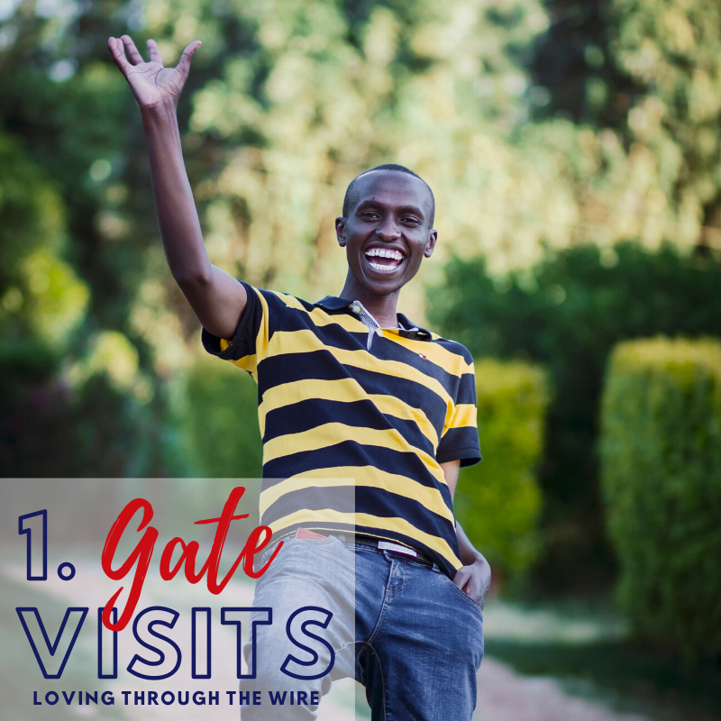 Gate visits - Loving through the wire.   Image on a smiling young man waving happily.