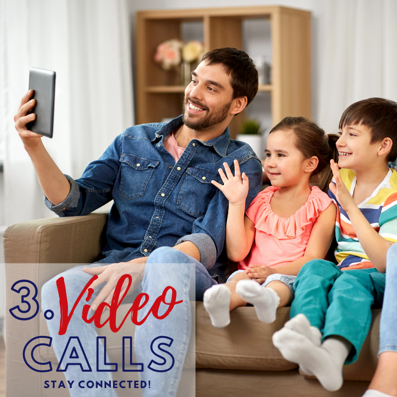 Video Calls - Stay connected  A happy dad sitting on a couch holds up a tablet. His two kids beside him smile and wave at the screen.